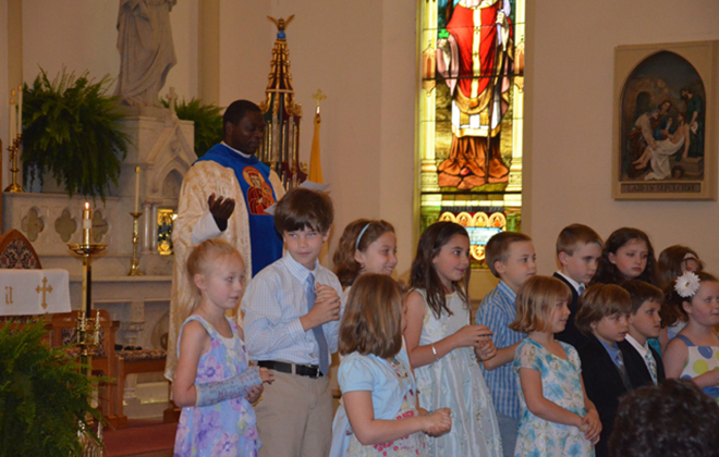 Young members of the parish recite the Litany of Our Lady during the crowning of the Blessed Mother's statue in May.
