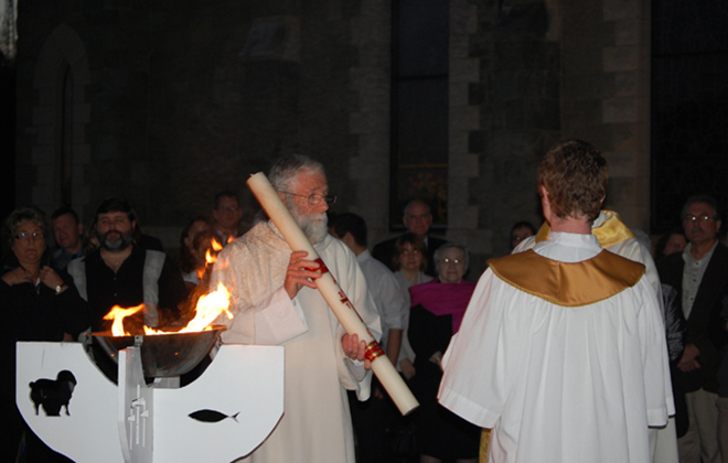 In the courtyard Deacon James Kledzik holds the paschal candle during the blessing of the new fire at the Easter Vigil.