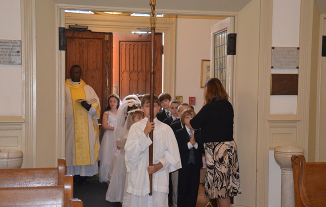Children of the parish walk in procession for the Mass at which they will receive their first communion.